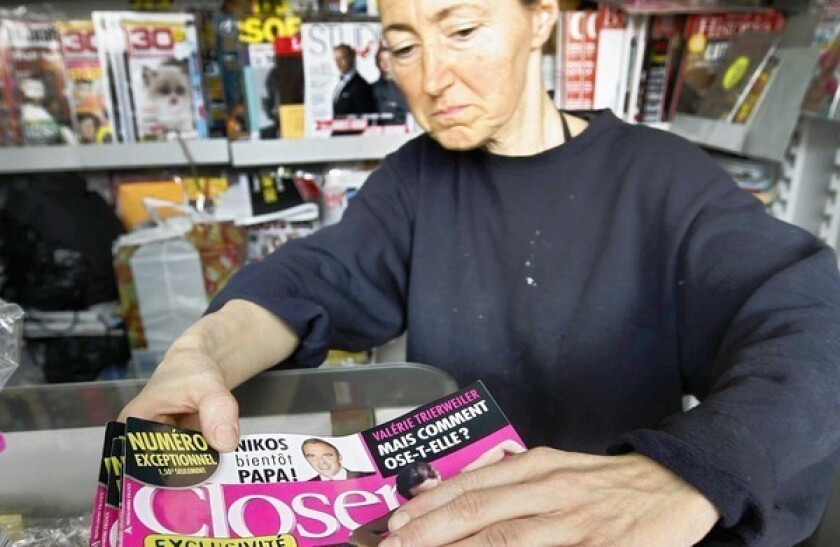 A newsstand clerk checks copies of Closer magazine Tuesday in Nice, southern France.