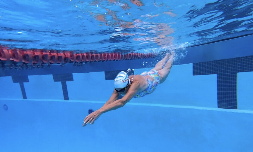 A senior swimmer glides underwater at the Rose Bowl Aquatics Center in Pasadena.
