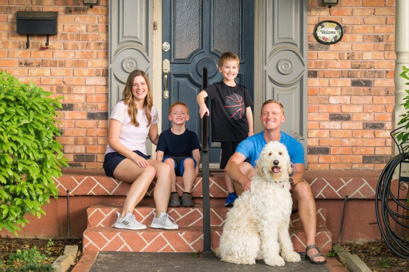 Shawn Ashmore and his family, dog included, sit on the steps outside their home.