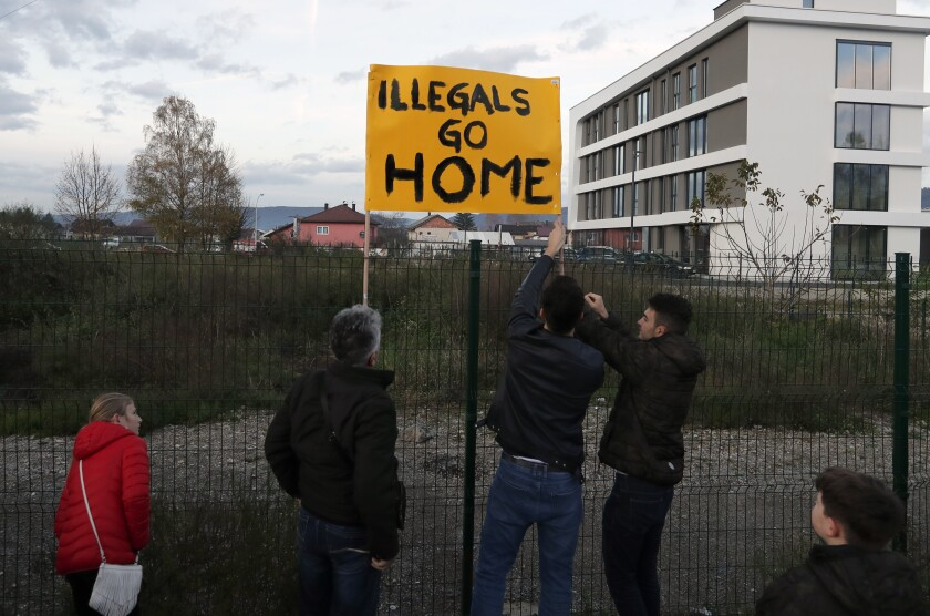 Protesters stand outside the Bira refugee camp in Bihac. Many Bosnians have expressed sympathy with migrants in view of their own war experience, but many also object to their presence.
