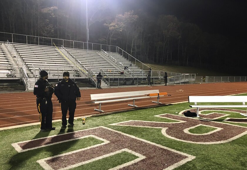 Police stand near empty grandstands at a high school in New Jersey.