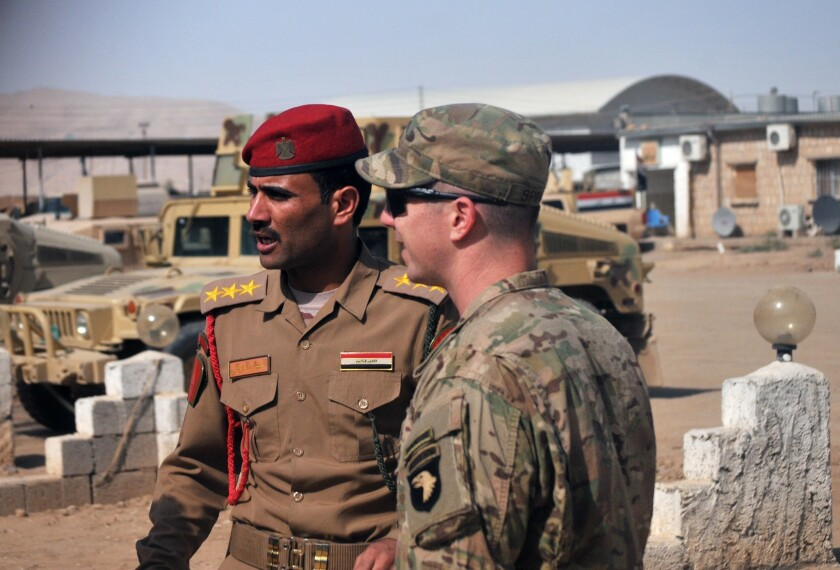 U.S. Army Capt. Gerrard Spinney, right, commander of Company C, 1st Squadron, 75th Cavalry Regiment, Task Force Strike, speaks to his Iraqi army counterpart from the Nineveh Operations Command before a security meeting at Camp Swift, Iraq.