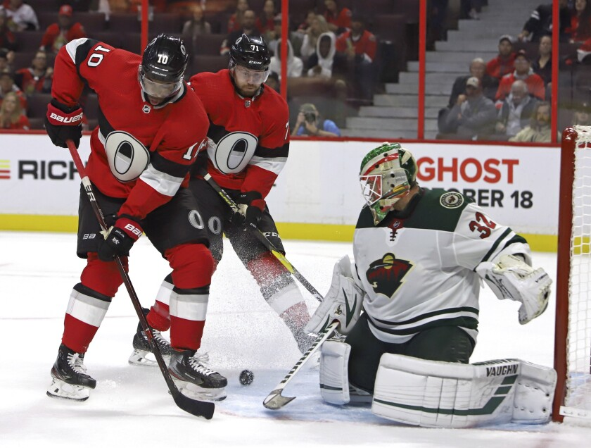 Minnesota Wild goaltender Alex Stalock (32) makes a save as Ottawa Senators left wing Anthony Duclair (10) and Senators center Chris Tierney (71) look for a rebound during second period NHL hockey action in Ottawa, Monday, Oct. 14, 2019. (Fred Chartrand/The Canadian Press via AP)