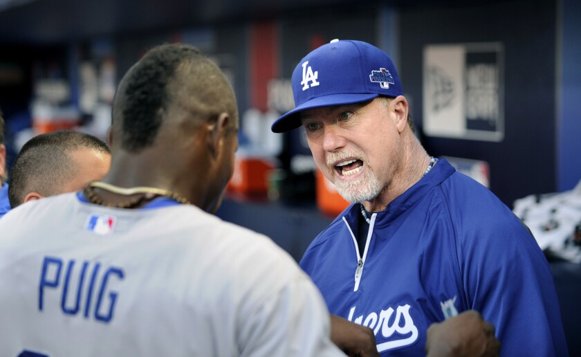 Dodgers batting coach Mark McGwire talks with outfielder Yasiel Puig during the 2013 playoffs.