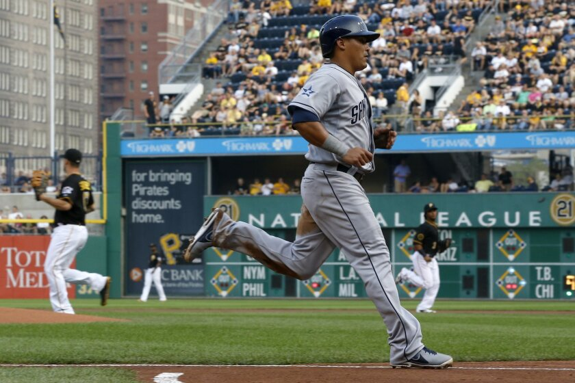 The Padres' Everth Cabrera, foreground, scores on a hit by Jedd Gyorko in the first inning of a baseball game against the Pittsburgh Pirates on Saturday, Aug. 9, 2014, in Pittsburgh.