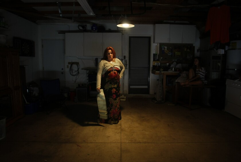 In her empty garage Lisa Twombly holds the contract for a used car she bought with a 21% dealer loan. The car soon needed repairs she felt the dealer should cover. When she quit making payments in protest, it was repossessed and set off a sequence of events that left Twombly and her 2 children homeless for 6 weeks.