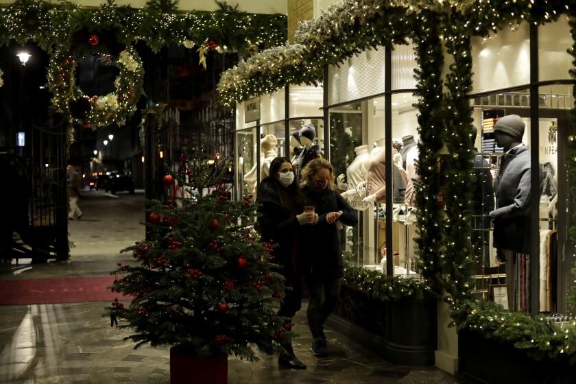 Unas mujeres con cubrebocas por el coronavirus pasan frente a una tienda de ropa en Burlington Arcade