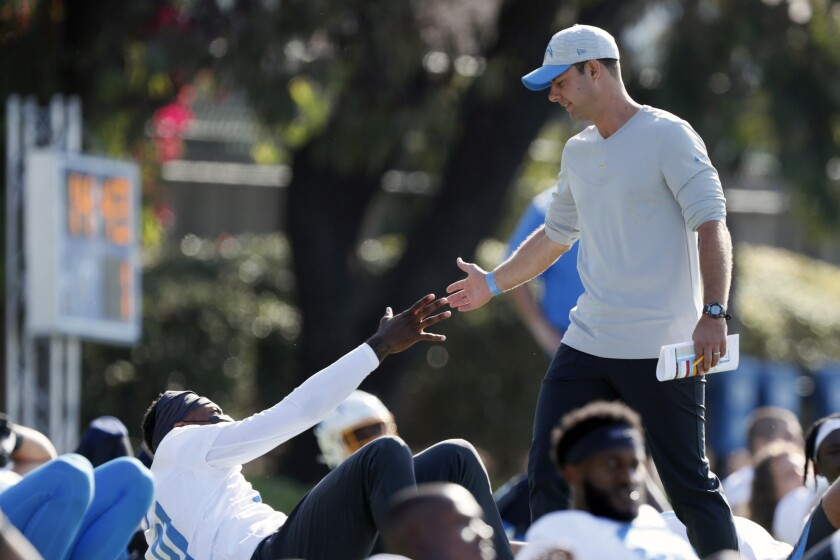 In this July 28, 2021 photo, Los Angeles Chargers head coach Brandon Staley greets wide receiver Mike Williams during practice at the NFL football team's training camp in Costa Mesa, Calif. As workers return to the office, friends reunite and more church services shift from Zoom to in person, this exact question is befuddling growing numbers of people: to shake or not to shake. (AP Photo/Alex Gallardo)