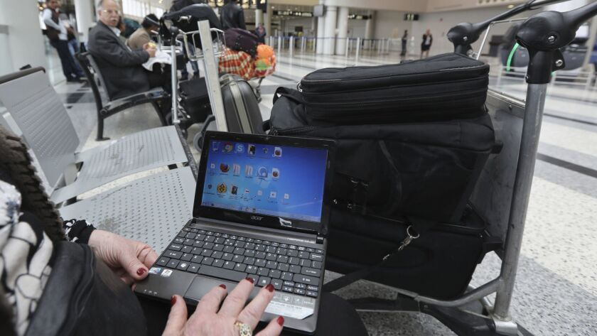 A Syrian woman traveling to the United States through Amman, Jordan, opens her laptop before checking in at Beirut's international airport.