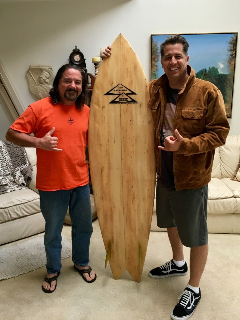 Bill Deneff (left) who came into possession of a rare Greek Surfboard he didn't know was stolen, with its owner, Jonathan Clark.