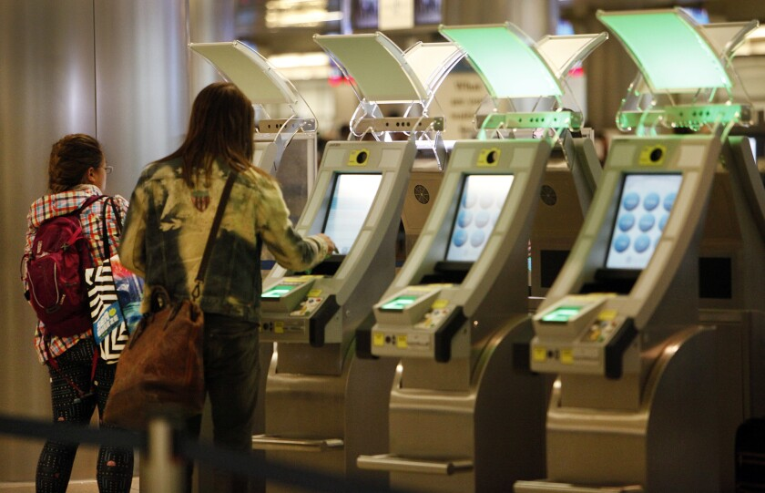 Passengers at the Tom Bradley International Terminal at LAX use the new automated passport-control kiosks that can read passports and customs declarations to expedite entry.
