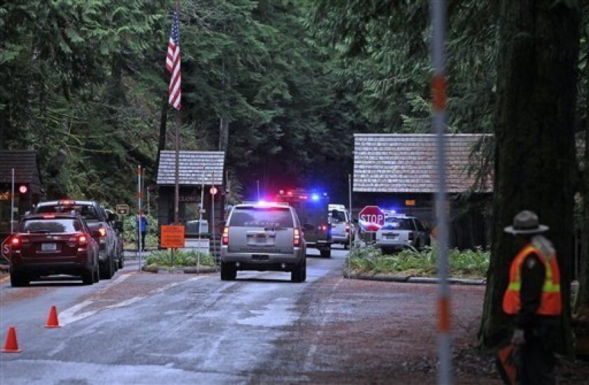 Emergency vehicles speed to the scene of a shooting of a Mount Rainier National Park ranger as another ranger redirects traffic in Mount Rainier, Wash., Sunday, Jan 1, 2012. A Mount Rainier National Park ranger was fatally shot following a New Year's Day traffic stop and authorities believed the gunman was still in the woods with an assault rifle. (AP Photo/The News Tribune, Dean J. Koepfler)