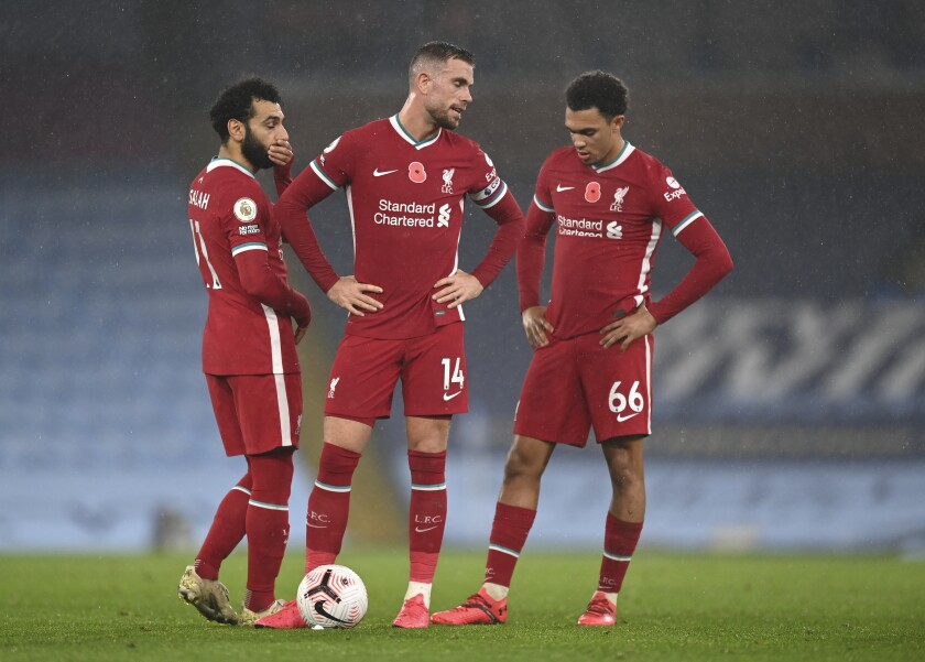 Liverpool's Jordan Henderson, center, and Trent Alexander-Arnold, right, and Mohamed Salah stand over the ball before taking a free kick during the English Premier League soccer match between Manchester City and Liverpool at the Etihad stadium in Manchester, England, Sunday, Nov. 8, 2020. (Shaun Botterill/Pool via AP)