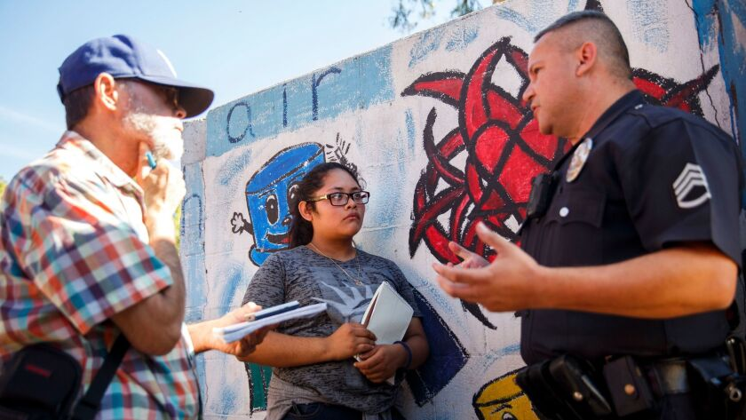 Senior Editor Antonio Mejias-Rentas, left, and student reporter Kimberly Gallardo, 16, of the Boyle Heights Beat newspaper interview a Los Angeles police sergeant for a report on a swap meet at the Ramona Gardens housing project.