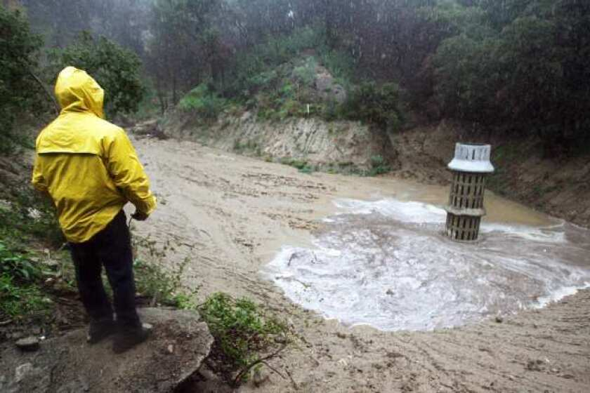A county officials inspects the flood control basin above Manistee Drive in La Canada Flintridge.