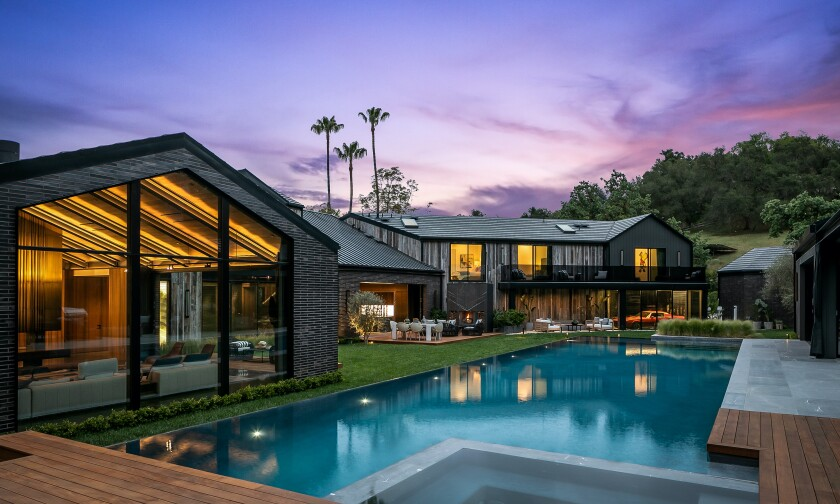 Built in 2021, this bold black farmhouse features a pool and guest house.