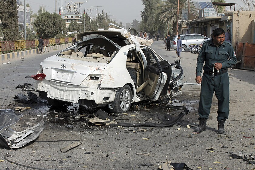An Afghan policeman investigates a damaged car following a bomb attack in southern Helmand province on Thursday.