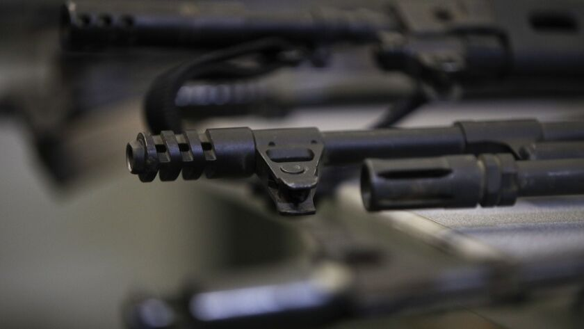 Illegally possessed firearms seized by authorities are displayed during a news conference Tuesday, O