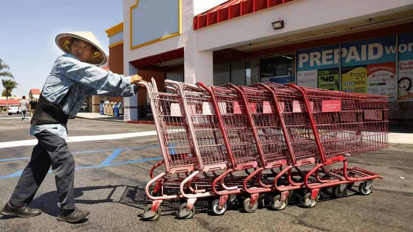 """Le Huynh, 56, collects shopping carts outside a supermarket in Garden Grove. """"I'm competing for the same work as the Latinos,"""" he says. """"The difference is I'm here legally."""""""