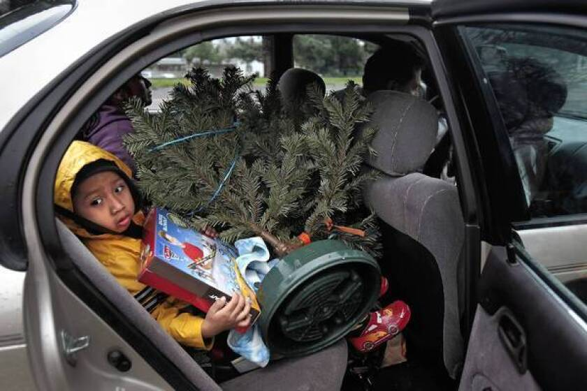 Cayetano Hernandez holds a Christmas tree in his lap that he and his family chose at a giveaway by the Delancey Street Foundation.