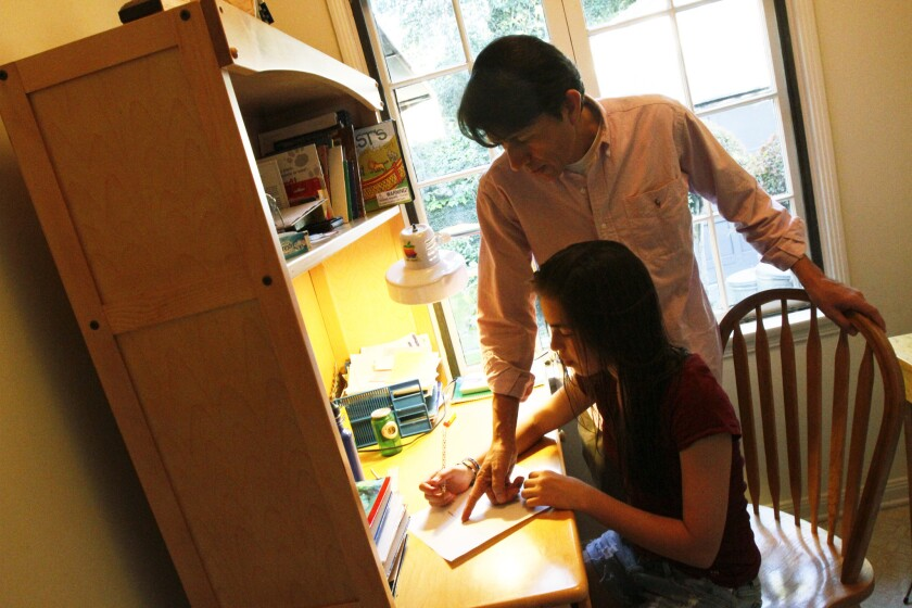 A dad helps his daughter with her eight-grade homework.