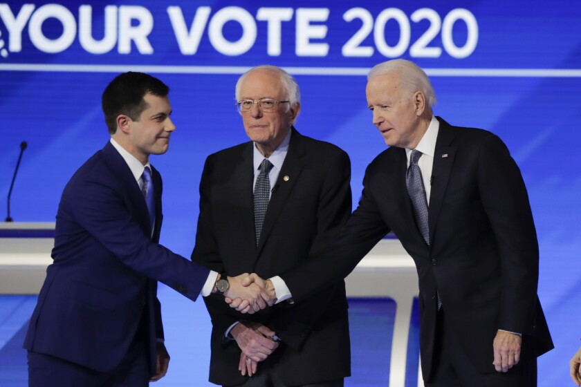 From left, Democratic presidential candidates former South Bend Mayor Pete Buttigieg, shakes hands with former Vice President Joe Biden as Sen. Bernie Sanders, I-Vt., watches Friday, Feb. 7, 2020, before the start of a Democratic presidential primary debate hosted by ABC News, Apple News, and WMUR-TV at Saint Anselm College in Manchester, N.H. (AP Photo/Charles Krupa)