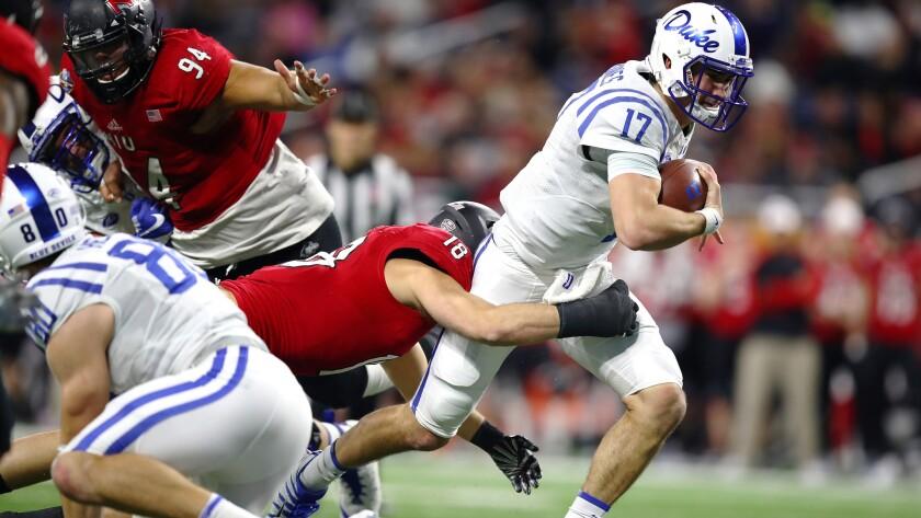 Duke quarterback Daniel Jones tries to break the tackle of Northern Illinois linebacker Alex Schwab during a run in the first half Tuesday night.
