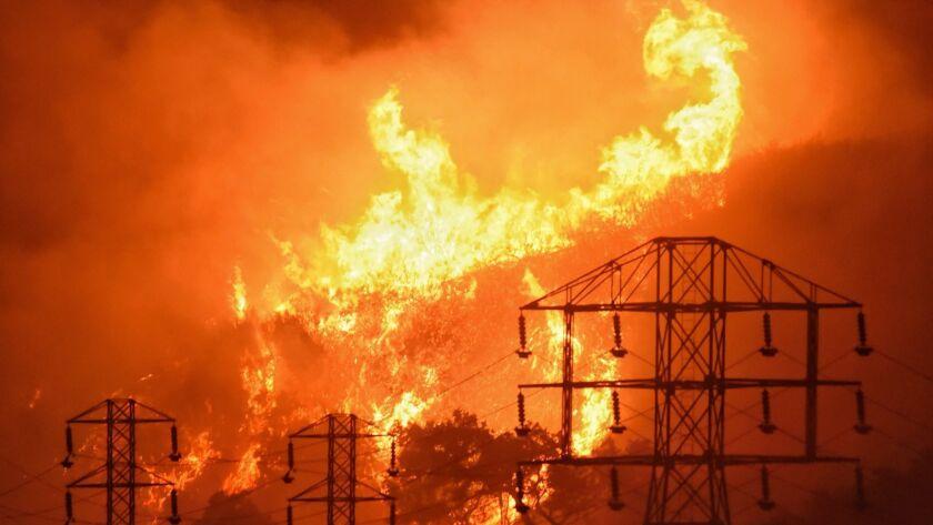 Flames burn near power lines in Montecito, Calif. on Dec. 16, 2017.