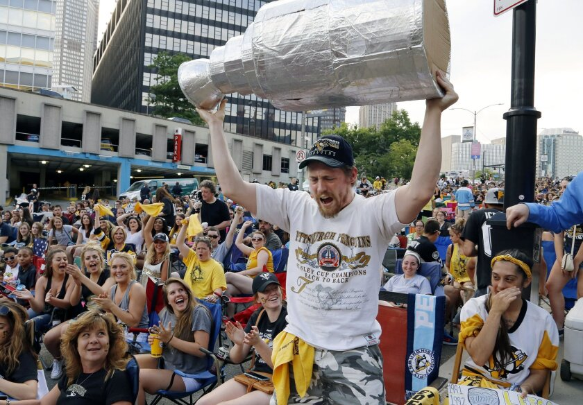 Pittsburgh Penguins fans cheer as Zac Crowe hoists a fake Stanley Cup outside Consol Energy Center before Game 2 of the NHL hockey Stanley Cup Finals between the Penguins and the San Jose Sharks on Wednesday, June 1, 2016, in Pittsburgh. (AP Photo/Gene J. Puskar)