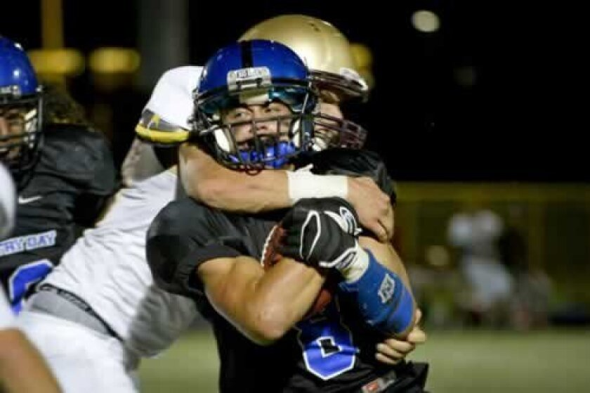A Bishop's School defender takes down a Country Day ball carrier. Photo by Andy Hayt