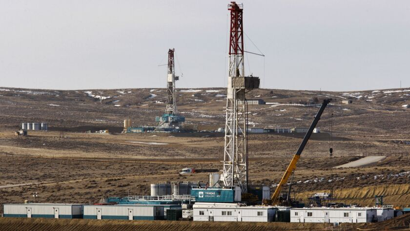 FILE- In this March 5, 2013, file photo, Trinidad Drilling rigs are seen off of Way Highway 59 outsi