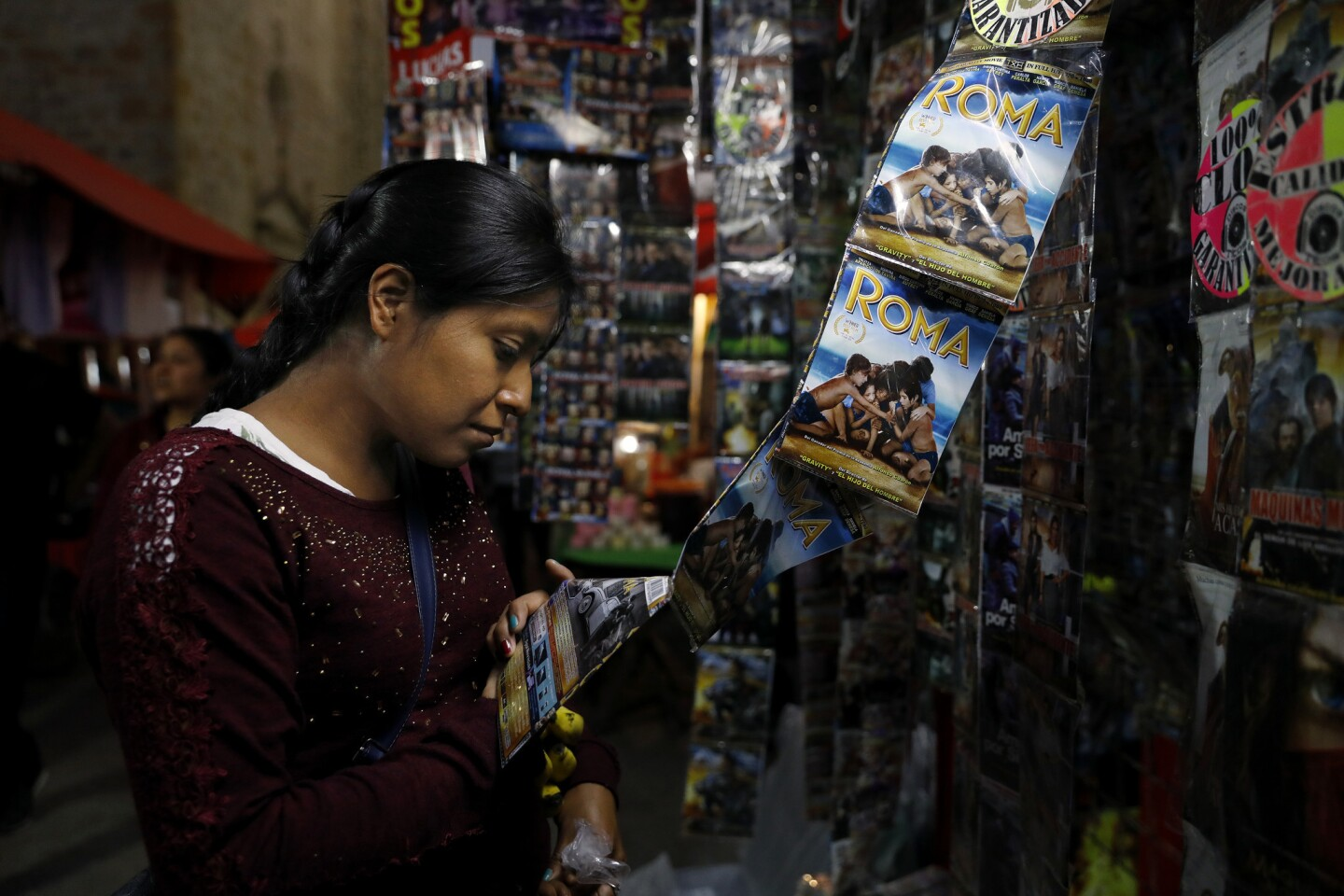 """Olivia Garcia Perez, 26, buys the movie """"Roma"""" in a market stand in Tlaxiaco, Mexico, the hometown of the movie's star, Yalitza Aparicio."""