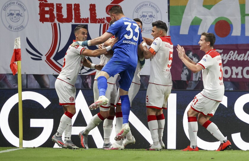 Duesseldorf's players celebrate after their side's second goal during the German Bundesliga soccer match between RB Leipzig and Fortuna Duesseldorf in Leipzig, Germany, Wednesday, June 17. 2020. Center are against Duesseldorf's Zanka and right Alfredo Morales. (Jan Woitas/Pool via AP)