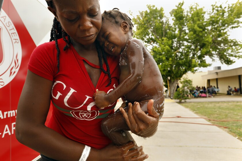 DEL RIO, TEXAS--JUNE 20, 2019--A young girl is bathed by her mother after they were just released fr