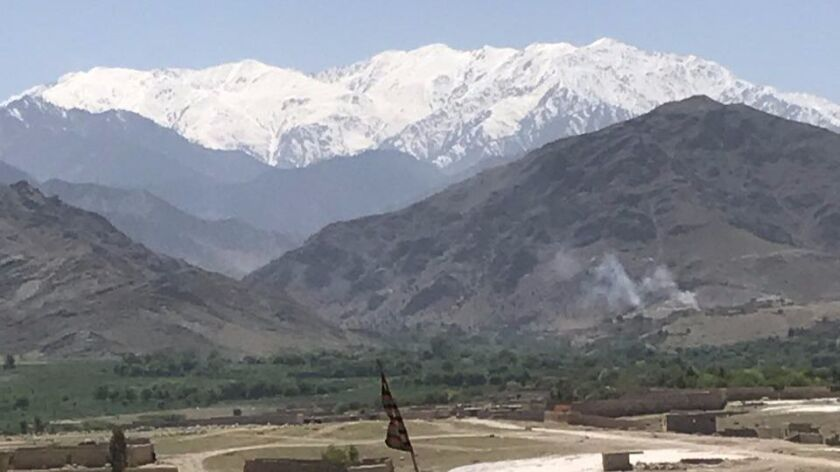 At right, smoke rises from Shodal village in eastern Afghanistan on Friday as U.S. and Afghan forces