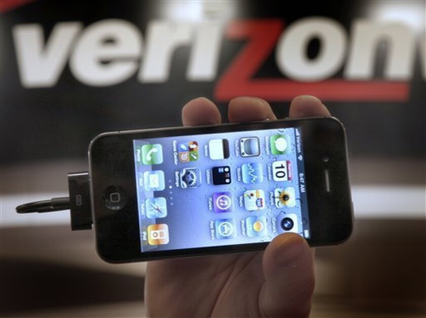 FILE - In this Feb. 10, 2011 file photo, Chris Cioban, manager of the Verizon store in Beachwood, Ohio, holds up an Apple iPhone 4G. Verizon Wireless, the nation's largest wireless carrier, joins competitors Thursday, July 7, 2011, as it gets rid of its unlimited data plan for new smartphone customers.(AP Photo/Amy Sancetta, file)