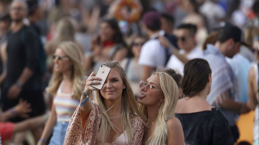 INDIO, CALIF. - APR. 13, 2018. A pair of women find room to take a selfie in the crowded grounds of