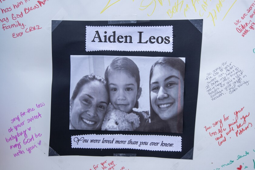 A poster with a photo of Aiden in between two people