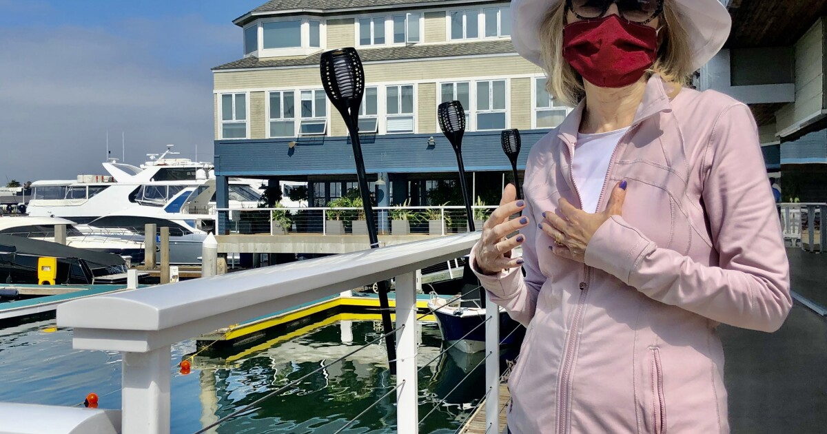 Column: A retired teacher leads the masked resistance in Newport Beach