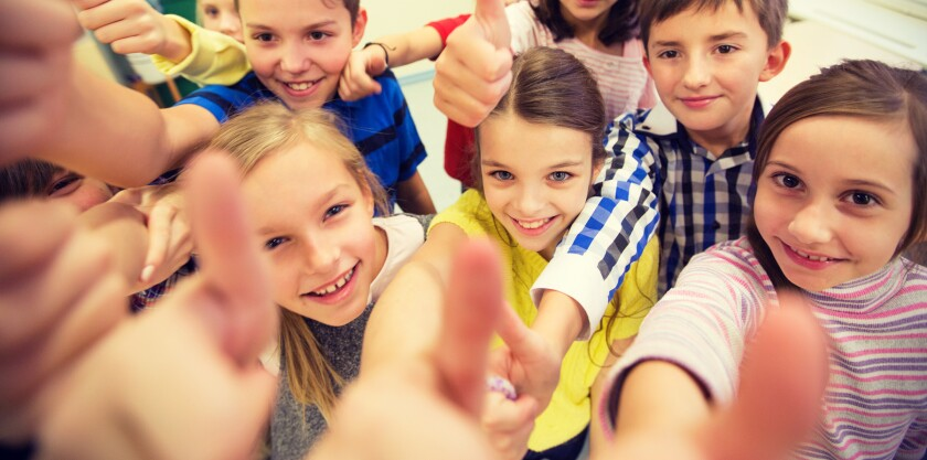 group of school kids showing thumbs up