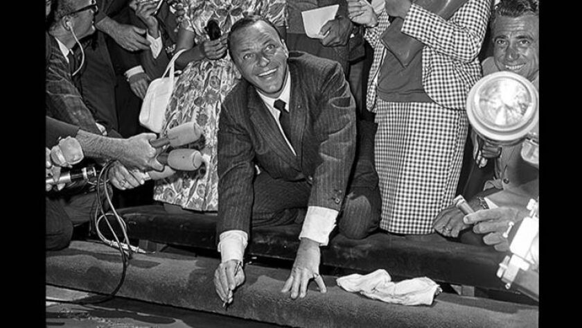 July 20, 1965: Frank Sinatra leaves his signature in cement at Grauman's Chinese Theatre in Hollywoo