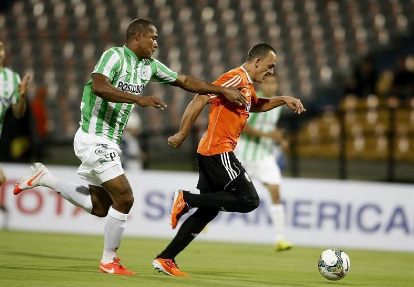 El jugador de Atlético Nacional de Colombia Alexis Henriquez (i) disputa el balón con Framber Villegas (d) del Deportivo La Guaira de Venezuela. EFE/Archivo
