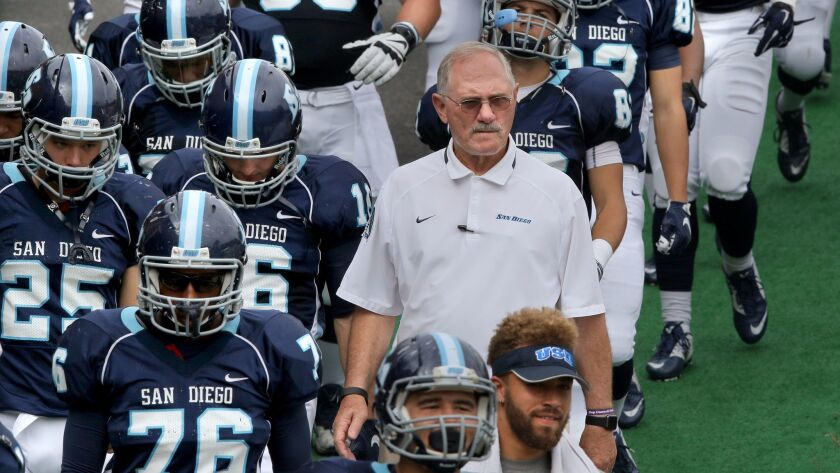 USD's Head Coach Dale Lindsey walks with his team into the stadium for the game.