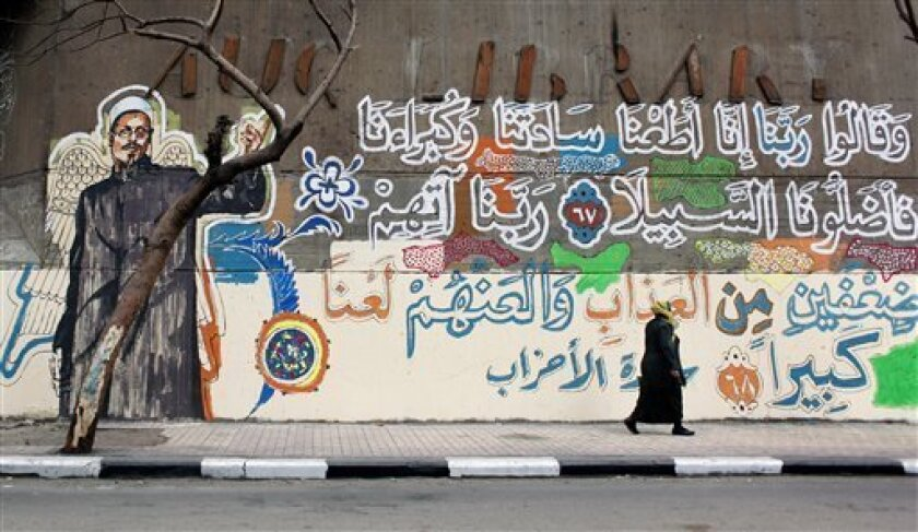 "An Egyptian woman walks past a mural with a picture depicting slain Azhar sheikh Emad Effat, who was killed during clashes between protesters and army soldiers in December 2011, with verses of Quran that read in Arabic ""God, we obeyed our lords and they misled us, punish them God twice as much and curse them"" in Cairo, Egypt Wednesday, Feb. 29, 2012. (AP Photo/Nasser Nasser)"