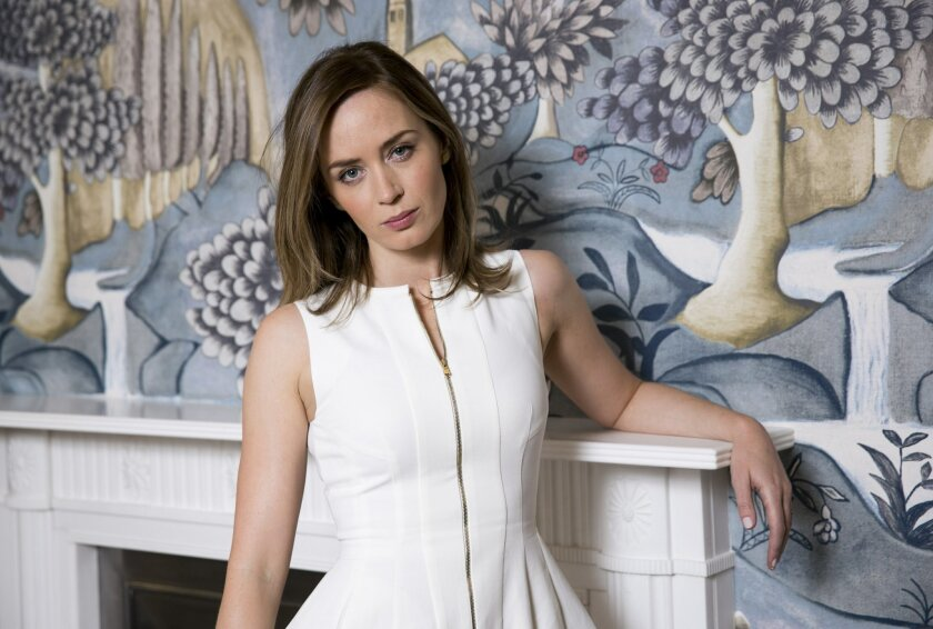 """In this Sunday, May 25, 2014 photo, actress Emily Blunt poses for a portrait in London. In her latest film, """"Edge of Tomorrow,"""" opening in the U.S. on June 6, 2014, the lithe British beauty wields big guns - of biceps and military-style variety - as Rita Vrataski, a Special Forces leader tasked with turning Tom Cruise's character from a scared pencil-pusher to a skilled warrior. Director Doug Liman said Blunt's character is """"the hero of the movie."""" (Photo by John Phillips Invision/AP)"""