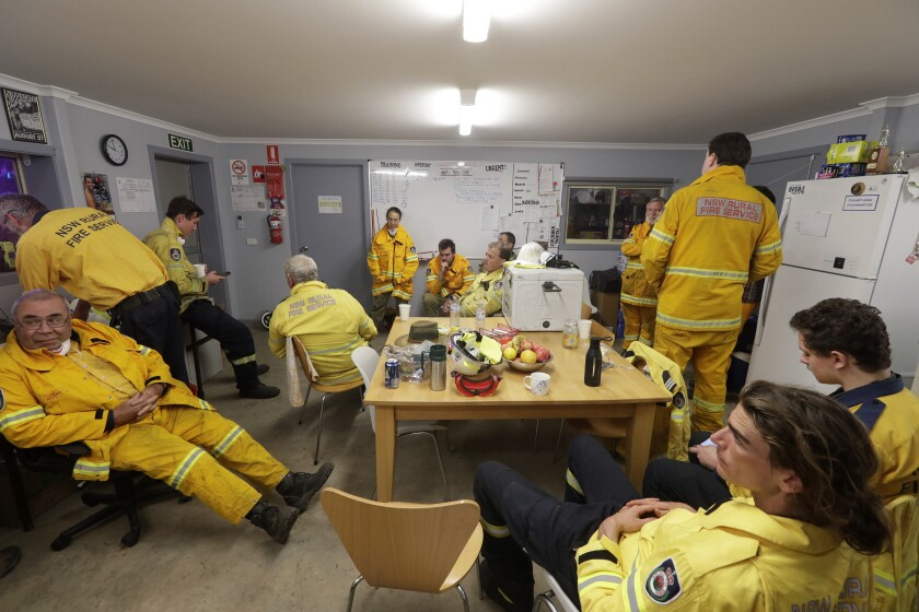 """In this Jan. 10, 2020, photo, firefighters and army personnel gather in a common room at the Rural Fire Service fire house at Burragate, Australia. It seemed imminent to those hunkering at the fire station that """"The Beast"""" would finally roar through. But on this night the wildfire only crept closer, prodding forward a few tentative fingers before going dormant again as the winds died. (AP Photo/Rick Rycroft)"""