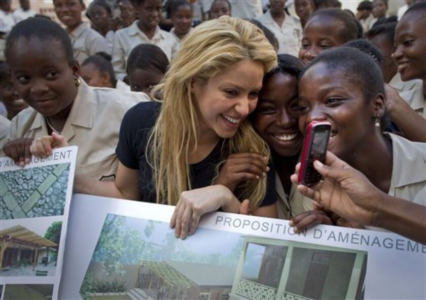 Colombian singer Shakira, center, has her picture taken with students at the  Elie Dubois public school during  a ceremony announcing the school's reconstruction project in Port-au-Prince, Haiti, Thursday, March 31, 2011. The Inter-American Development Bank and Shakira's Barefoot (Pies Descalzos)