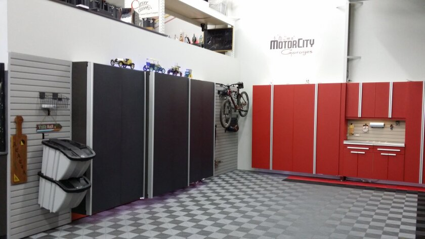In this photo provided by courtesy of Motor City Garages, new cabinetry designed for the garage makes it easier for homeowners to improve the appearance and storage capabilities of their garages. (Motor City Garages via AP)