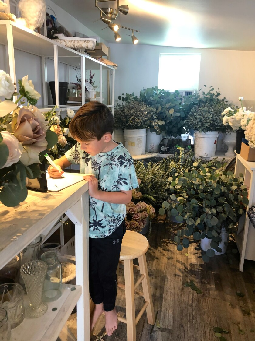 First-grader Ezekiel Evans does distance learning at his mom's flower shop. Nestor Language Academy remains closed.