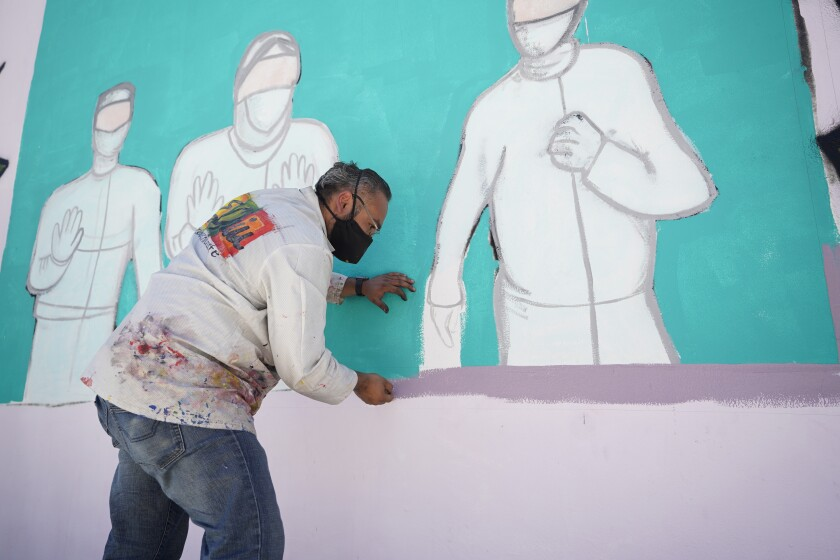 Artist Enrique Chiu painting on the mural project.